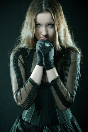 Pretty gothic girl praying over black Stock Photo - 12148490
