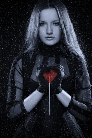 Cold gothic girl in corset with red sweet heart in her hands photo