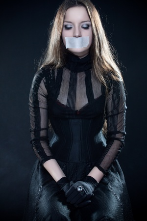 Pretty gothic girl in corset with sealed mouth looking down photo