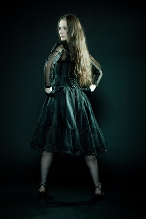 Pretty gothic girl posing over black background photo