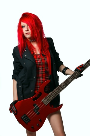 Redhead rocker girl in red dress with red bass guitar isolated over white