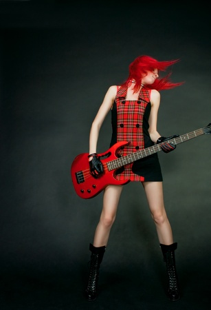 Redhead rocker girl posing over dark photo