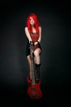 rocker girl: Redhead chica rockera en el vestido rojo con el bajo de color rojo