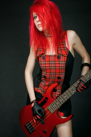 Redhead rocker girl with guitar posing over dark background