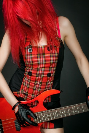 rocker girl: Redhead chica rockera posando sobre fondo oscuro