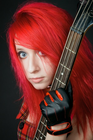 Redhead rocker girl posing over dark with guitar photo
