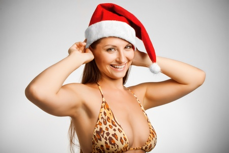 Pretty funny girl in bikini and in Santa's hat posing over white Stock Photo - 12162077
