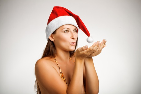 Pretty funny girl in bikini and in Santa's hat posing over white Stock Photo - 12162047