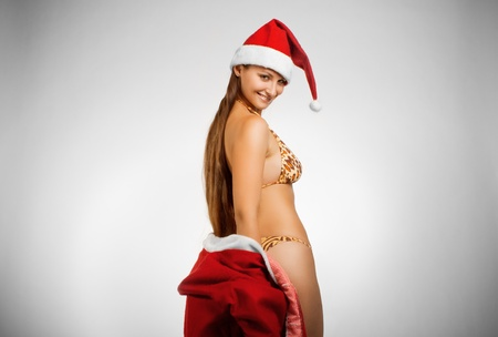Pretty funny girl in bikini and in Santas hat posing over white background photo
