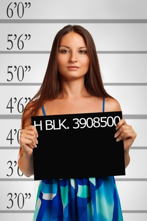 pretty prisoner in blue dress posing over white photo