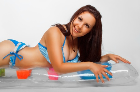 Pretty girl in bikini on an inflatable mattress posing over white background Stock Photo - 12214106