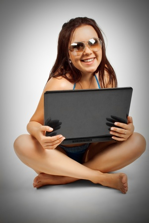 Pretty funny girl in bikini posing with laptop over white Stock Photo - 12162078