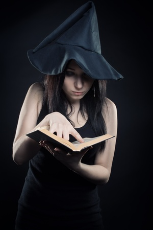 wizardry: Pretty young girl in witch hat reading spell book over dark background Stock Photo