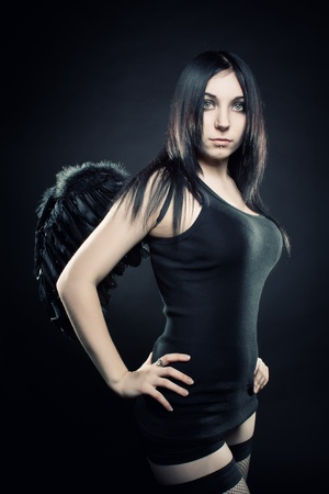 Pretty girl with wings posing over dark background photo
