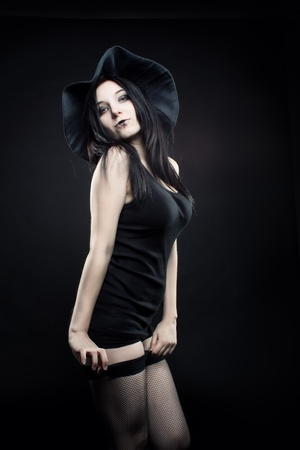 Pretty  sexy girl in witch hat posing over dark background photo