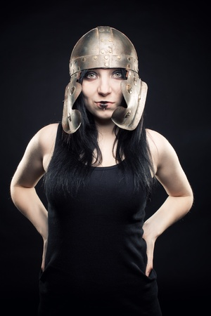 Pretty girl with roman helmet posing over dark background Stock Photo - 12163212