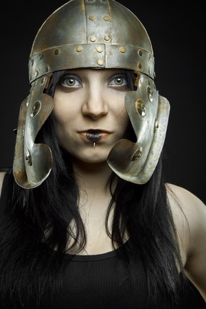 Pretty sexy girl with ancient roman helmet posing over dark background. photo