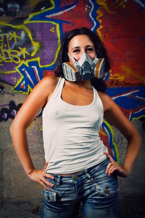 Postnuclear funny girl with gas mask posing over graffiti photo