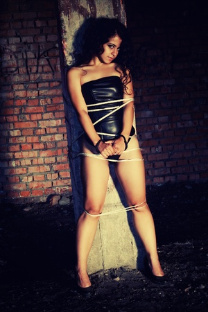 Pretty young woman tied with a rope in the dark old building Stock Photo - 12163516