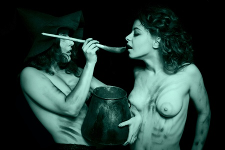 paganism: Two dirty nude witches with kettle posing over dark Stock Photo