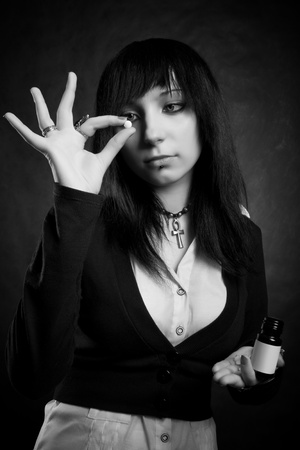 pretty gothic girl with pill posing over dark Stock Photo - 12162893