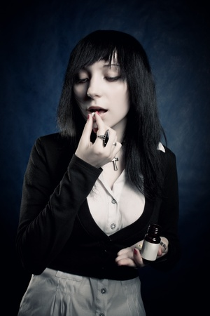 Pretty gothic girl eating tablet over blue photo