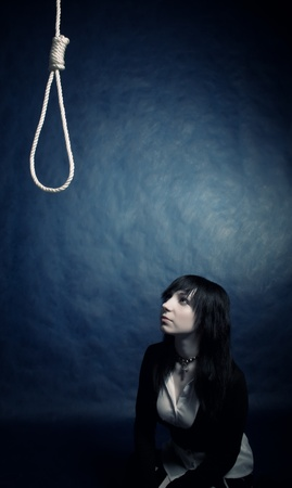 pretty gothic girl looking to the gallows over dark photo