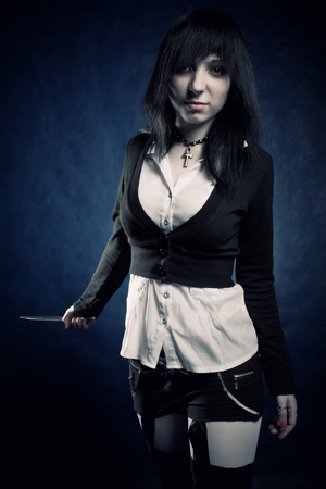 pretty gothic maniac girl posing with knife over blue photo