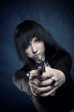 Pretty gothic girl with gun posing over blue photo