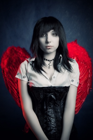 Prettty gothic girl with red wing posing over dark Stock Photo - 12162906