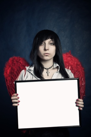 Pretty gothic girl with red wings holding photo frame over blue Stock Photo - 12160718