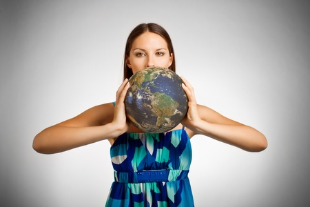 Pretty girl holding globe over white photo