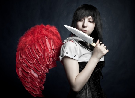 pretty gothic girl with red wings and knife posing over dark photo