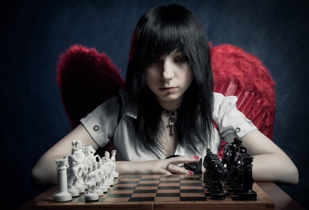 Pretty angel looking to chessboard over dark background photo