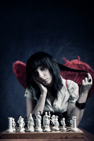Pretty gothic girl with wings playing chess photo