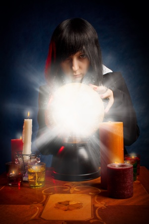 Gothic girl with a crystal ball and candles posing over dark photo