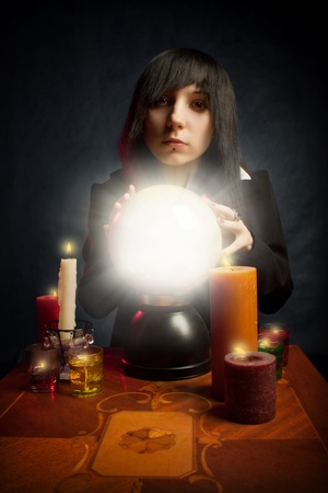 presage: Gothic girl with a crystal ball and candles posing over dark