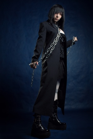 pretty gothic girl bounded by chains posing over dark photo