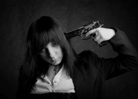 regret: pretty gothic girl with gun posing over dark