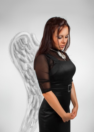Pretty girl in black dress with wings posing over white. photo