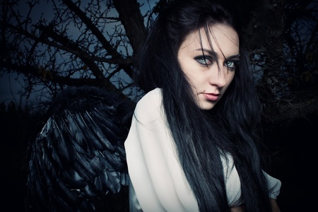 pretty dark-haired angel in the cold autumn forest photo