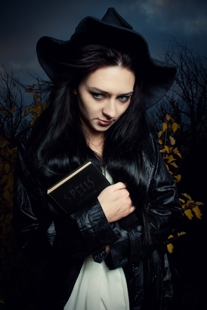 pretty witch standing in autumn forest with spells book