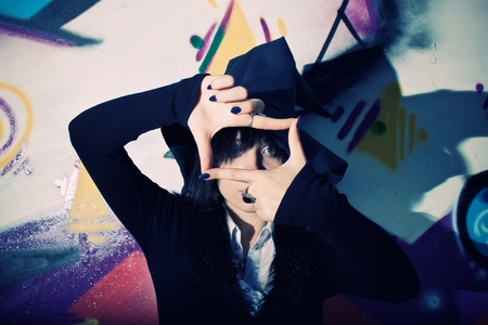 Pretty young witch in hat posing over wall with graffiti Stock Photo - 12163203