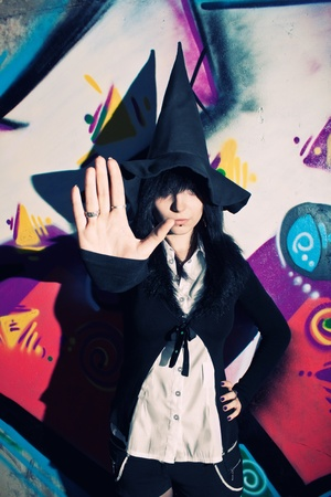 witchery: Pretty young witch in hat posing over wall with graffiti Stock Photo
