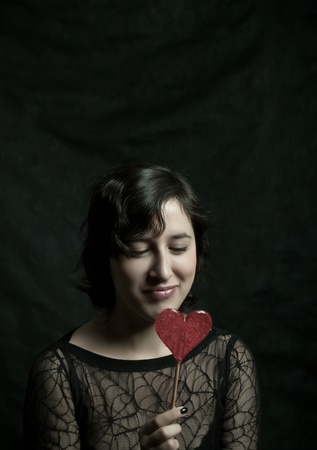 girl with heart-shaped lollipop posing over dark Stock Photo - 12162891