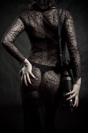 Pretty girl with camera posing over dark background Stock Photo