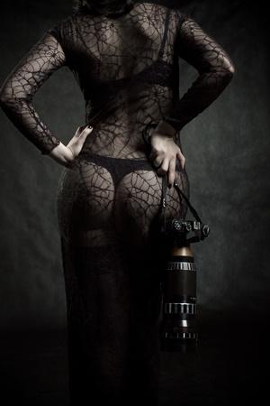 Pretty girl with camera posing over dark Stock Photo - 12163506
