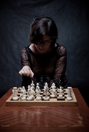 Pretty girl in black playing chess over dark background photo
