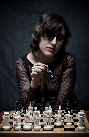 Pretty girl playing chess over dark Stock Photo - 12163266