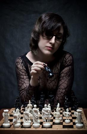 Pretty girl playing chess over dark Stock Photo - 12163266